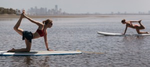 MIAMI, FL - JULY 10:  Yoga instructor Sarah Henry  leads a class during a paddleboard yoga session at Adventure Sports Miami on July 10, 2011 in Miami, Florida. The paddle board is said to give the body?s core more of a workout then in a gym since the platform is unstable and one must use the muscles to remain balanced on the board.  (Photo by Joe Raedle/Getty Images)