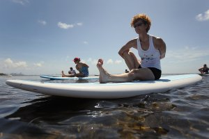 woman-participates-paddleboard-yoga-class-water